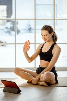 Yoga teacher conducting virtual yoga class at home on a video conference