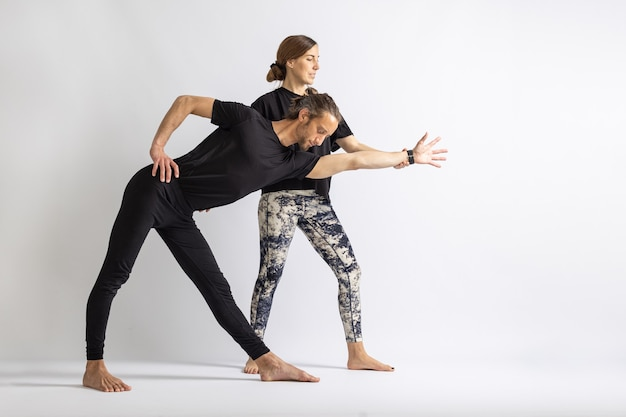 Yoga teacher correcting posture to her student isolated on white background