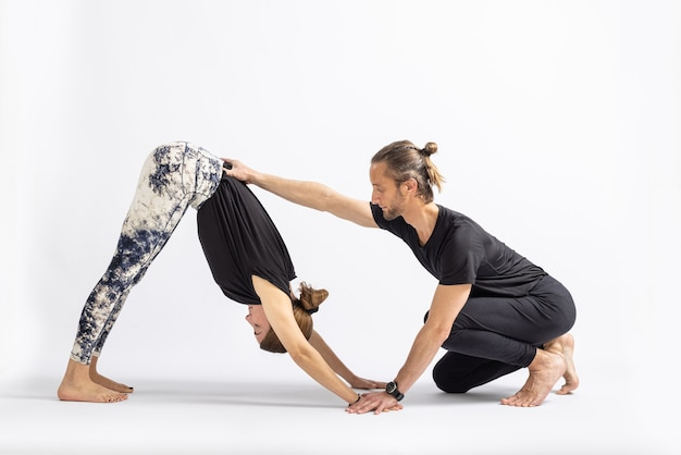 Yoga teacher correcting posture to his student isolated on white background