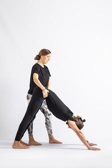 Учитель йоги корректирует осанку своему ученику, изолированному на белом фоне