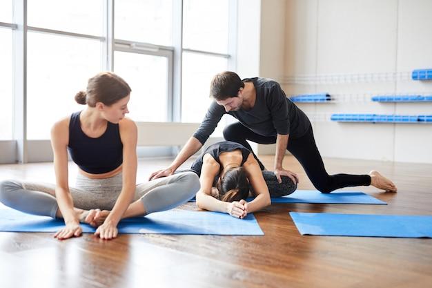 Учитель йоги поправляет ученика в классе