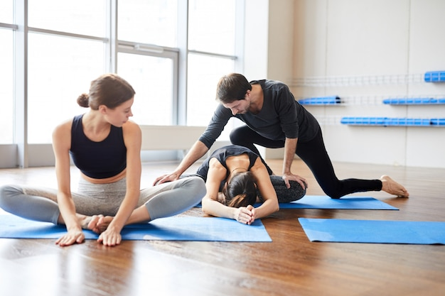 Yoga teacher correcting student at class