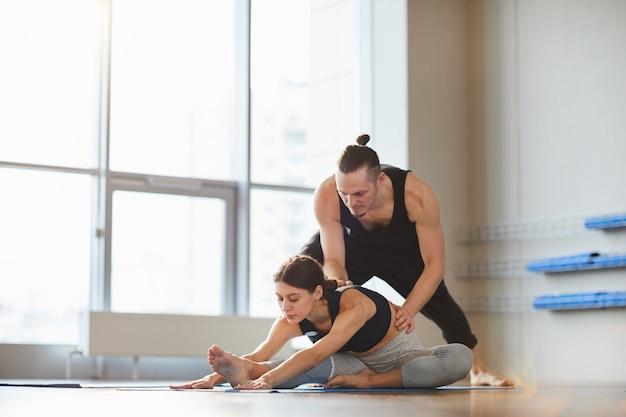 Учитель йоги помогает девушке согнуться