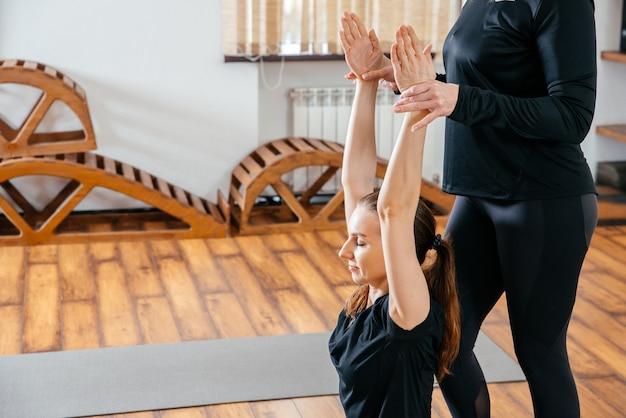 Учитель йоги помогает молодой женщине принимать позы в тренажерном зале