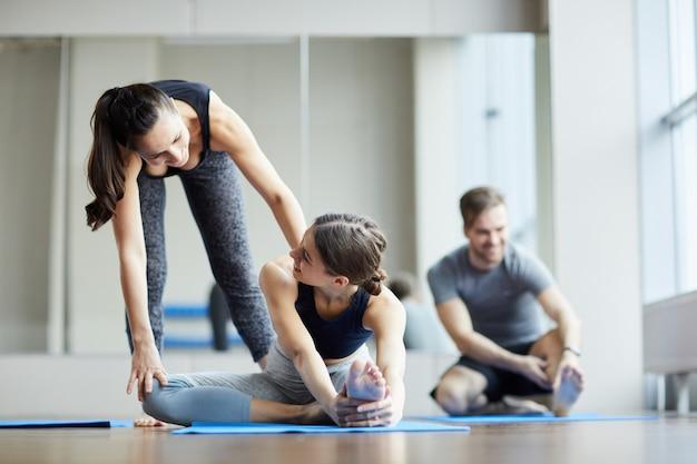 Yoga teacher pushing back of student