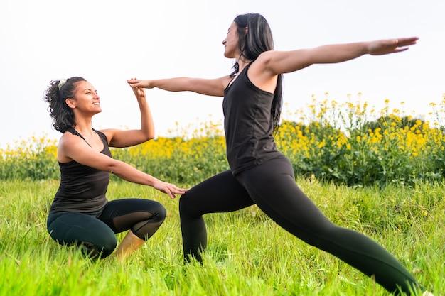 Yoga teacher teaches student a position in green park