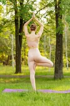 ヨガ講師の女性が早朝に都市公園でヨガを練習します