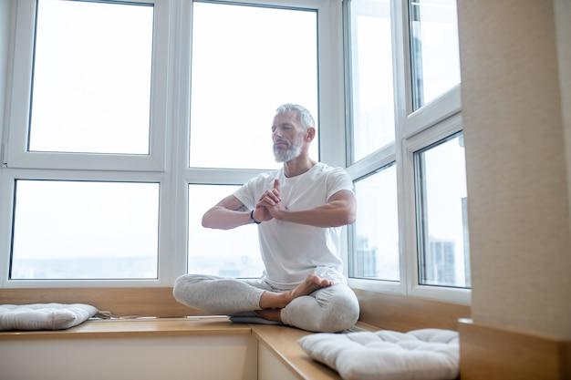 ヨガの時間。ヨガをして集中して見える白いtシャツの白髪の男