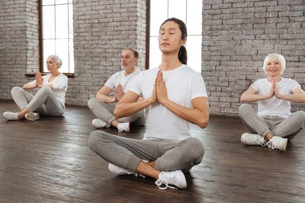 ヨガの時間。瞑想しようとしている胸の前で手をつないでいる退職者のグループ