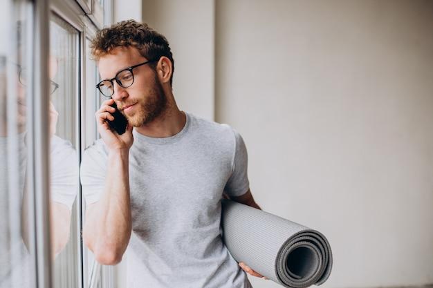 Istruttore di yoga con tappetino che parla al telefono e in piedi vicino alla finestra