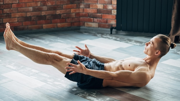 Yoga training for abs muscles stamina and endurance. physical activities for strong body and healthy mind. man exercising in a gym.
