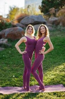 Занятия йогой на открытом воздухе. крупным планом обучения спортивных людей, в активной одежде, стоя в позе воина, зеленый газон природного парка