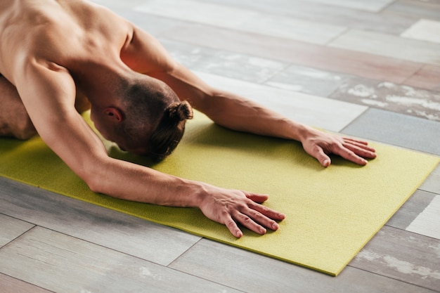 Yoga training. sport and fitness. wellness lifestyle and regular gym workout. man exercising on a mat. stretching flexibility and endurance.