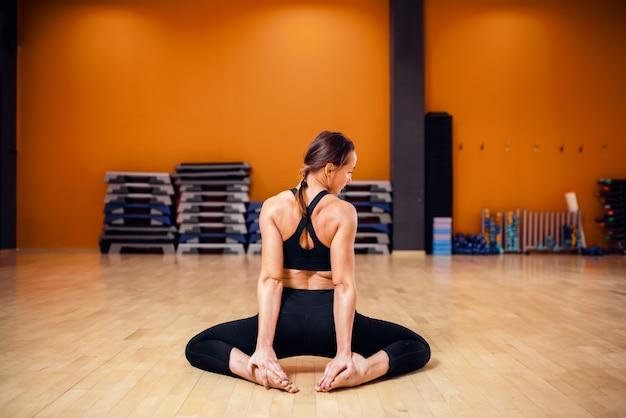 ヨガのトレーニング、ストレッチ運動、背面図、屋内でのトレーニングを行うスポーツウェアの女性。ジムでのヨギ教室、健康的なライフスタイル