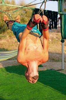 Йога-процедура для кора, качели йоги, стройный молодой человек привязан к четырем доскам над землей, мужчина развивает выносливость и растягивает корпус.