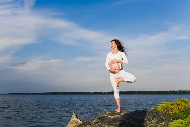 妊娠中の女性によるヨガツリーポーズ。