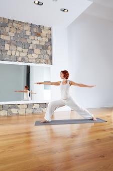 Yoga warrior two ii pose in wooden floor