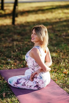 Женщина йоги на зеленой траве в позе лотоса