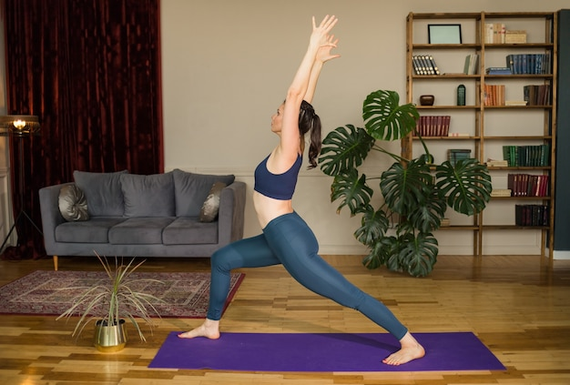 Yoga woman performs pose virabhadrasana on a rug in a room