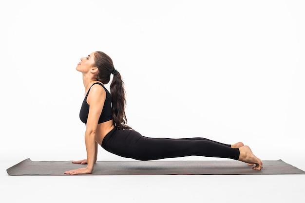 Женщина йоги - симпатичная брюнетка в активной одежде занимается йогой на белой поверхности