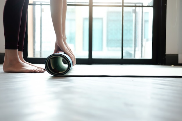 Yoga woman rolling her lilac mat after a yoga class