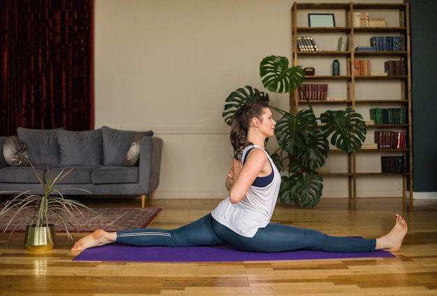 Yoga woman in sports clothes performs splits on a mat in the room