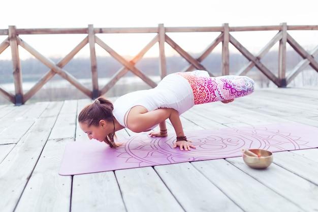 自然の中でヨガポーズエクササイズを行うエクササイズマットのヨガ女性筋力トレーニング