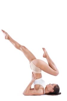 Женщина йоги с совершенным телом практикуя йогу представляет во всю длину в студии изолированной на белизне. упражнения на баланс.