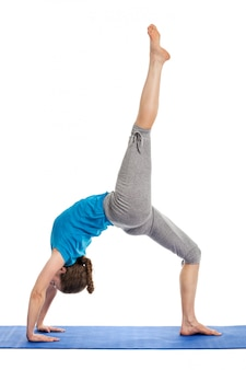 young attractive woman in the dhanurasana pose studio