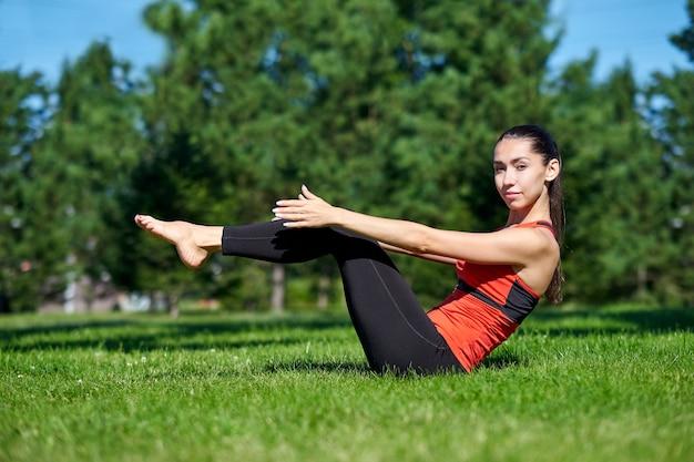 ヨガ。公園で自然の中でヨガ瞑想を練習している若い女性。健康ライフスタイルのコンセプト。