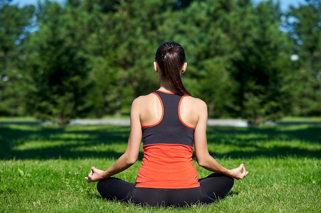 ヨガ。公園で自然の中でヨガ瞑想を練習している若い女性。蓮華座。健康ライフスタイルのコンセプト。
