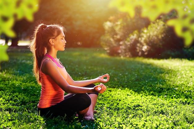 Йога. йога молодой женщины практикуя или танцы или протягивать в природе на парке. концепция здорового образа жизни