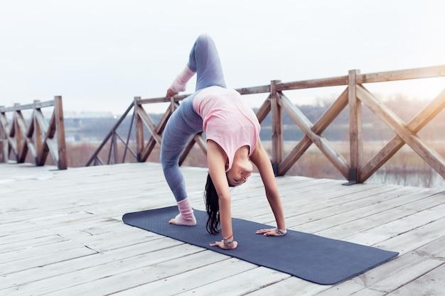 Yoga young yogi woman practices yoga asana fourlimbed staff pose in nature background