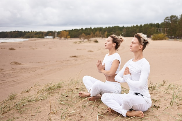 Yoga, zen, enlightenment, reacreation, meditation and concentration concept. young male and female wearing white clothes meditating with eyes closed, making namaste gesture, sitting in lotus pose
