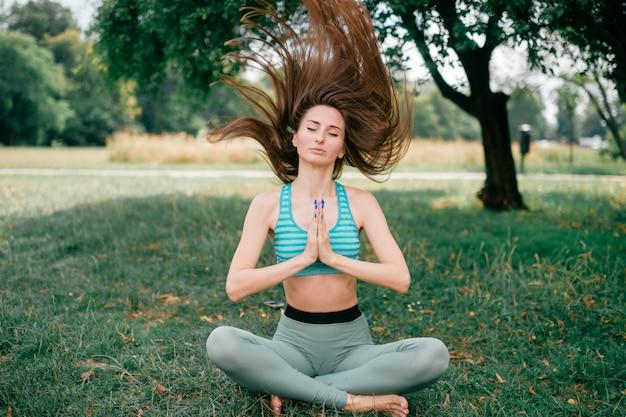 Девушка фитнеса брюнет делая парк лета yogain.