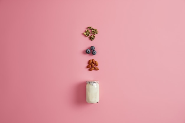 Yoghurt, pumpkin seeds, blueberry and almond nut on pink  background. ingredients for healthy nourishing breakfast. preparing delicious snack. balanced dieting and proper nutrition concept