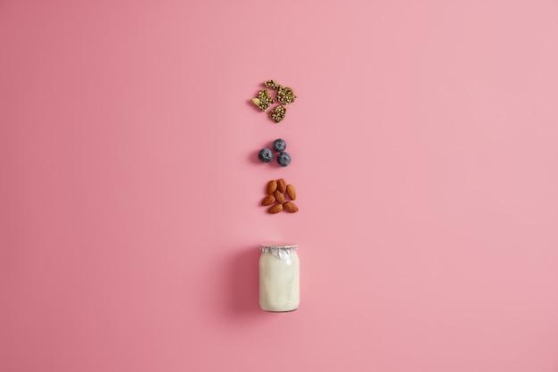 ピンクの背景にヨーグルト、カボチャの種、ブルーベリー、アーモンドナッツ。健康的な栄養のある朝食のための成分。美味しいおやつを用意しています。バランスの取れたダイエットと適切な栄養の概念