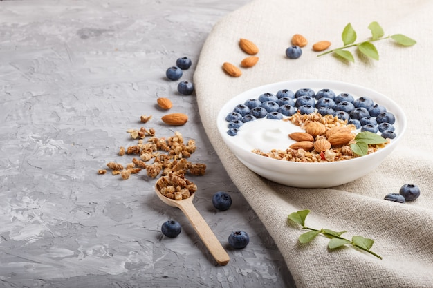 Yoghurt with blueberry, granola and almond in white plate with wooden spoon on gray concrete background. side view.