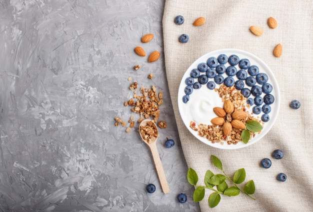 Yoghurt with blueberry, granola and almond in white plate with wooden spoon on gray concrete background. top view.