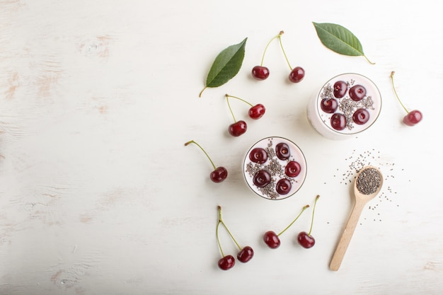 Yoghurt with cherries, chia seeds and granola in glass with wooden spoon. top view background