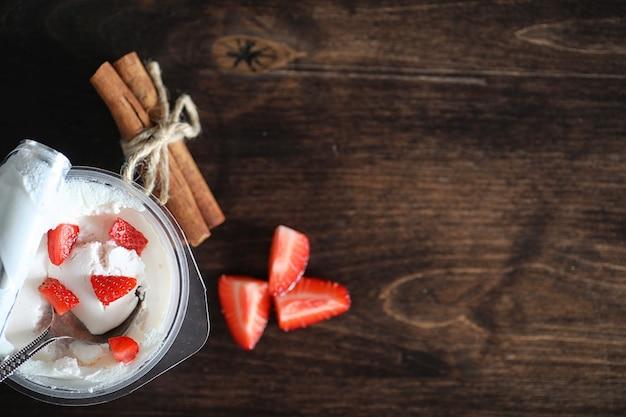 Йогурт со свежей сочной клубникой и вишней на деревянном столе