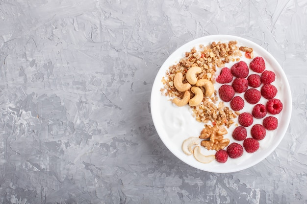 Yoghurt with raspberry, granola, cashew and walnut in white plate  on gray concrete background and linen textile