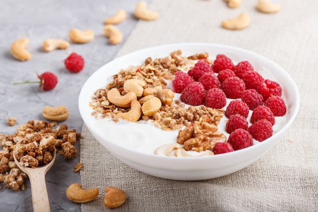 Yoghurt with raspberry, granola, cashew and walnut in white plate with wooden spoon on gray concrete background and linen textile. side view.