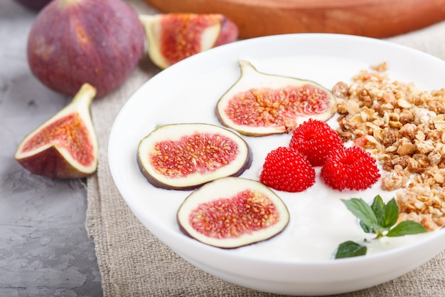 Yoghurt with raspberry, granola and figs in white plate on a gray concrete background
