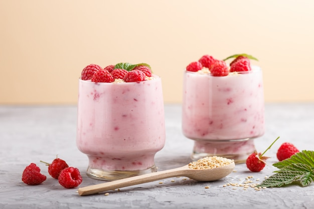 Yoghurt with raspberry and sesame in a glass and wooden spoon on gray surface. side view.