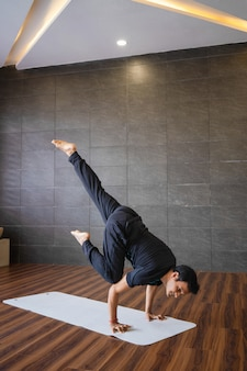 Yogi doing advanced hand stand yoga pose in gym