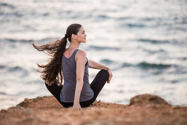 Yogi girl does twisting on a cliff by the sea