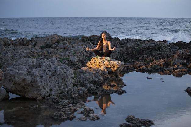 蓮のヨギの女の子は夜の海の近くの岩の上でポーズします。