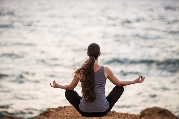 Yogi girl in lotus position on a cliff by the sea