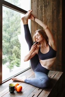 A yogi girl performs a complex exercise while sitting at the window. in her hand is a cup of green tea